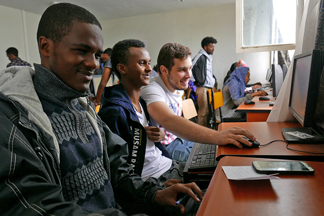 Dimitri Karev, A.B. '21 (right) reviews coursework with Ethiopian high schoolers in the AddisCoder program. (Photo courtesy of AddisCoder)