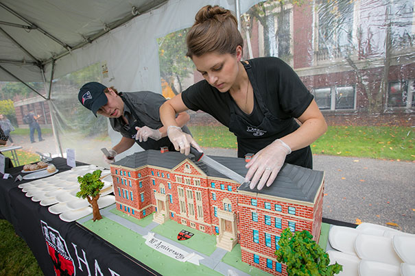 Caterers make the first cut into a birthday cake baked in the shape of Pierce Hall. Eliza Grinnell/SEAS Communications