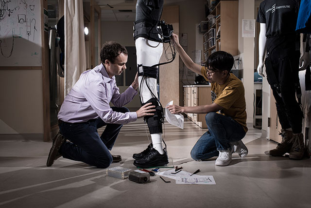 Conor Walsh and his Graduate Student Jaehyun Bae fine-tuning an ankle-assisting exosuit. Credit: Rolex Awards/Fred Merz