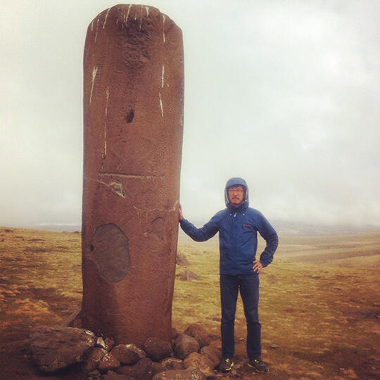 Winston Yu stands next to a Vishap stone in Armenia