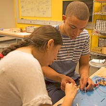 Mechanical engineering concentrator Bryant Huggins, S.B. '19 (right) and UTEC student Anarea Alvarez Veva collaborate to test the circuits for the team's microfluidic device. (Photo by Adam Zewe/SEAS Communications)