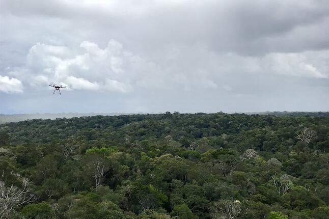 A drone flies towards a rain storm in the Amazon
