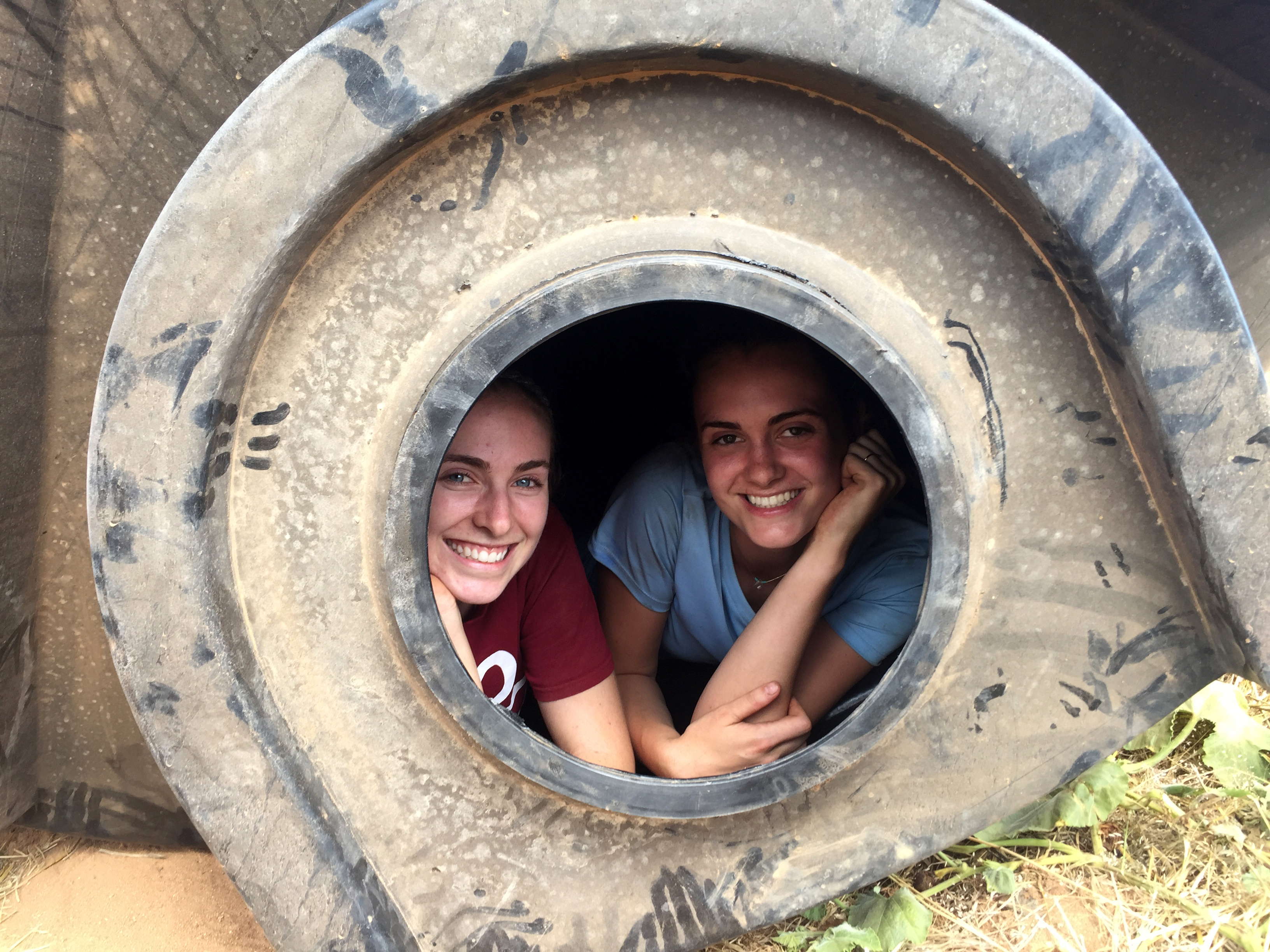 Sophie Pesek, S.B. '20 and Nicole Trenchard, S.B. '20 pose inside of a tank after installing the bulkhead connection that will allow Mkutani teachers to dispense water from the systems. The tank openings were so small that only a few members of the team could crawl in with headlamps and wrenches to tighten fittings. (Photo by Jerry Bowling)