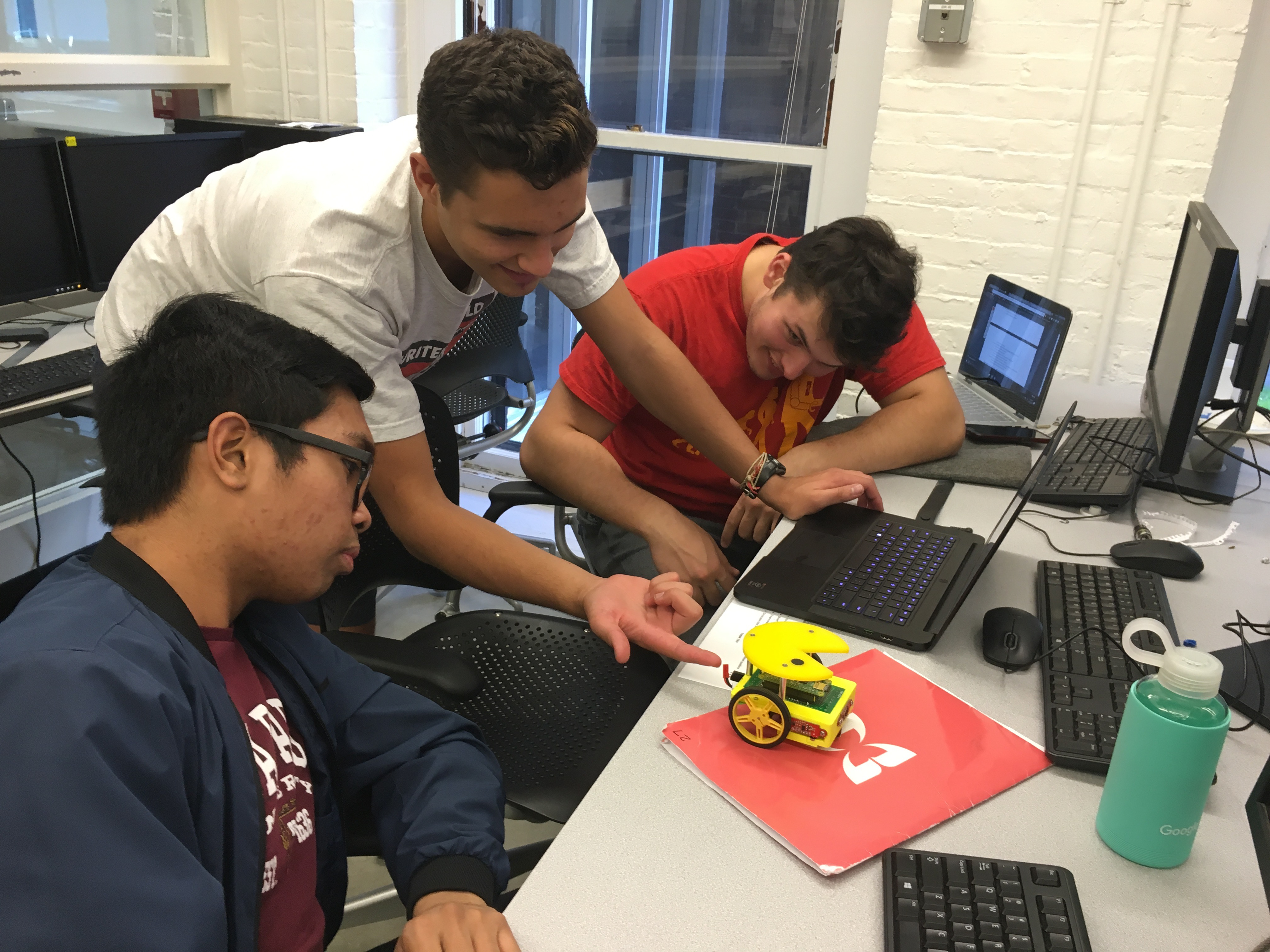 (From left) Freshman Robert Malate, Charlie Colt-Simonds, S.B. '20, an electrical engineering concentrator, and Andrew Meersand, S.B. '20, a mechanical engineering concentrator, inspecting the Pacbot robot. (Photo provided by HURC.)