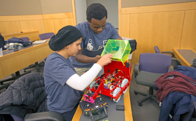 Competitors Marwah Sabrah A.B. '21 and Daniel Getega, S.B. '19, an electrical engineering concentrator, make last minute adjustments to their robot before entering the arena for the ES51 Turf Wars. (Photo by Alana Davitt/SEAS Communications)